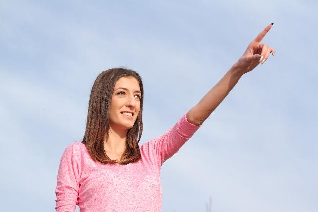 空を指さす外国人女性