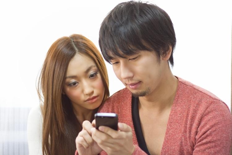 スマートフォンを見る男女