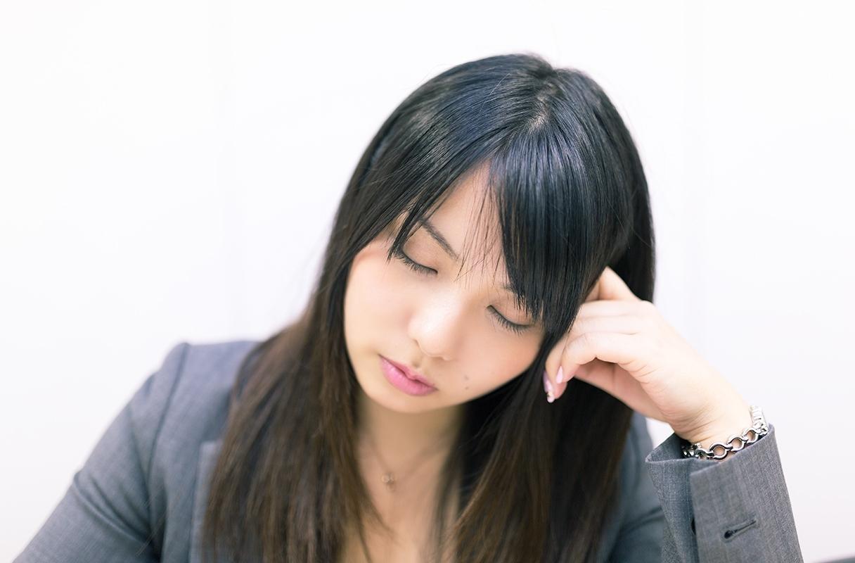 肘をついて居眠りする女性