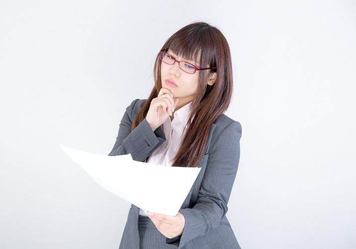 書類を見て悩む女性会社員
