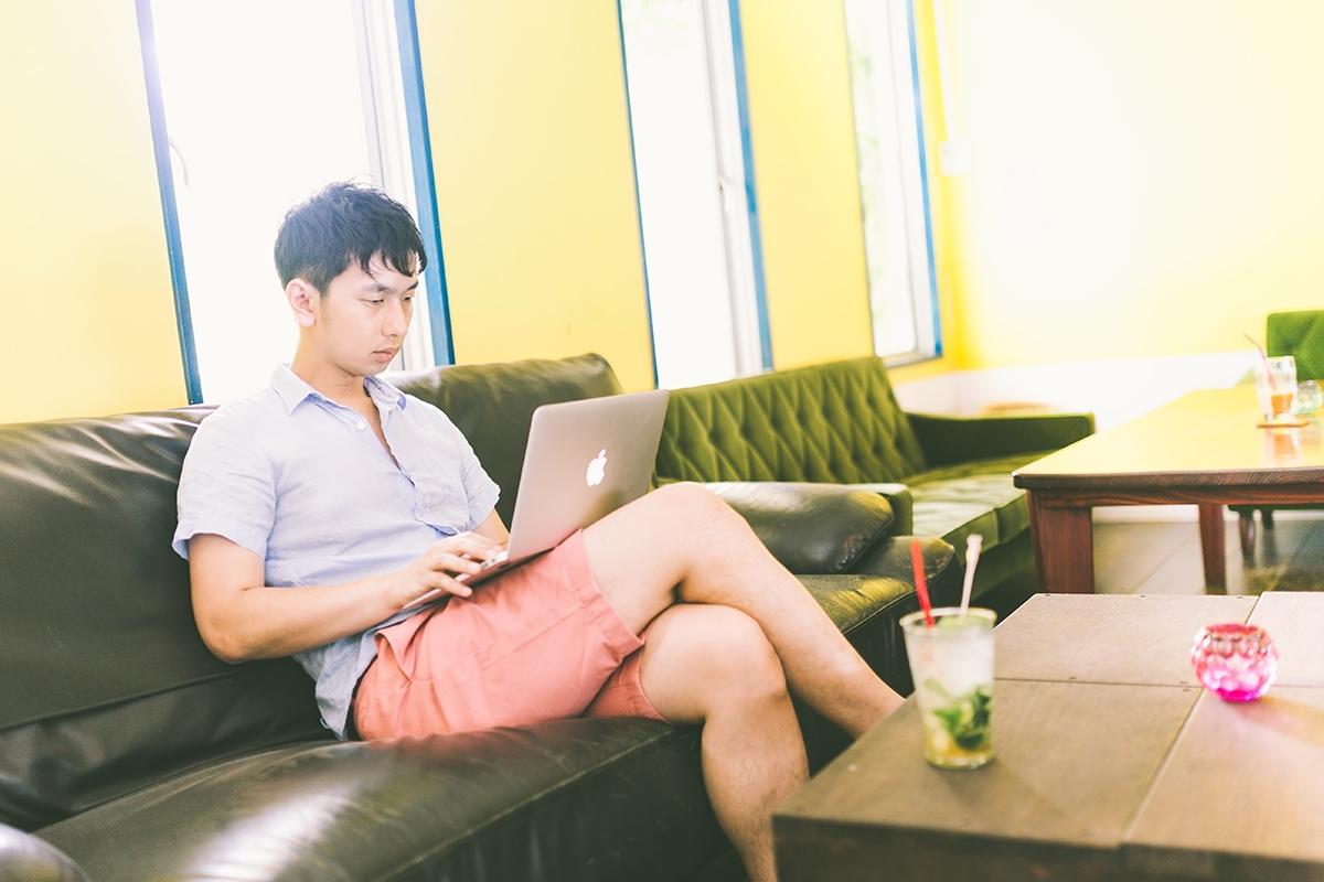 ソファーでパソコンを使う男性