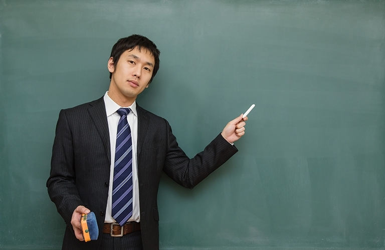 黒板の前で指導する会社員