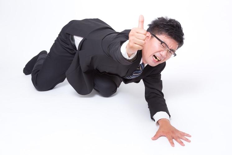 倒れ込んで親指を立てる会社員