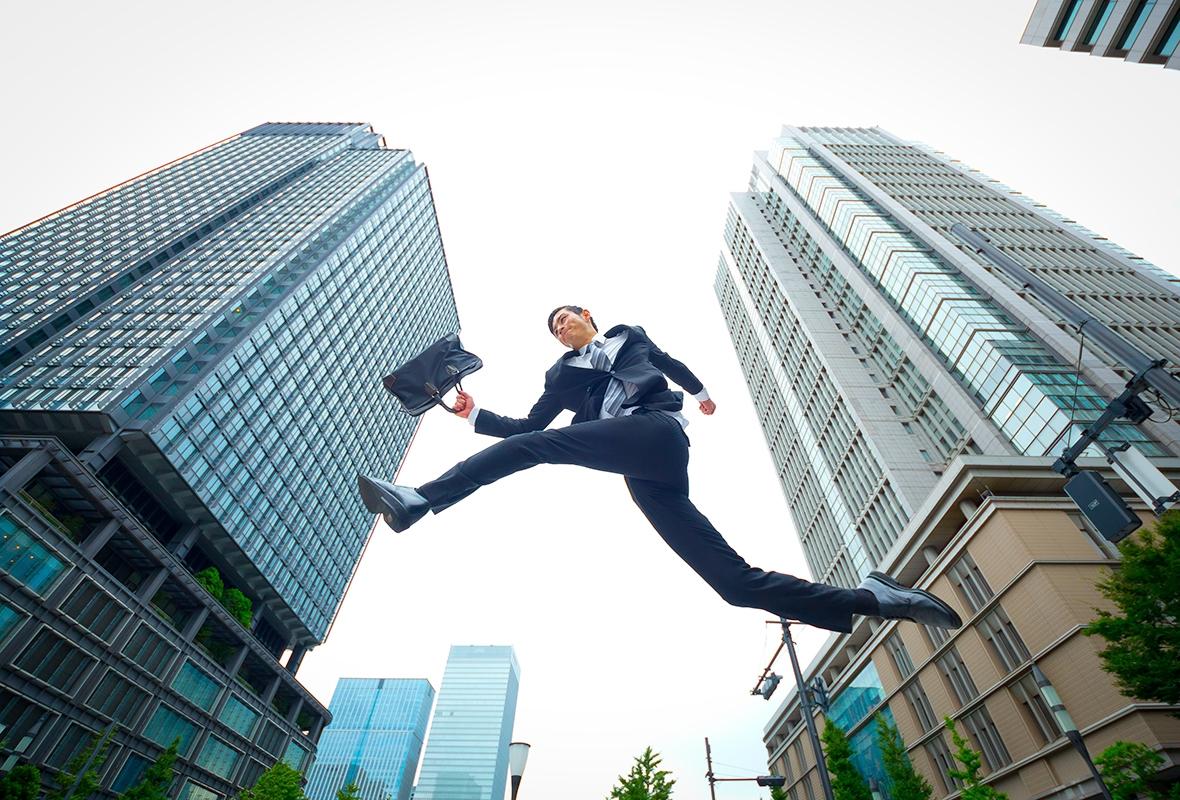 オフィス街でジャンプするサラリーマン