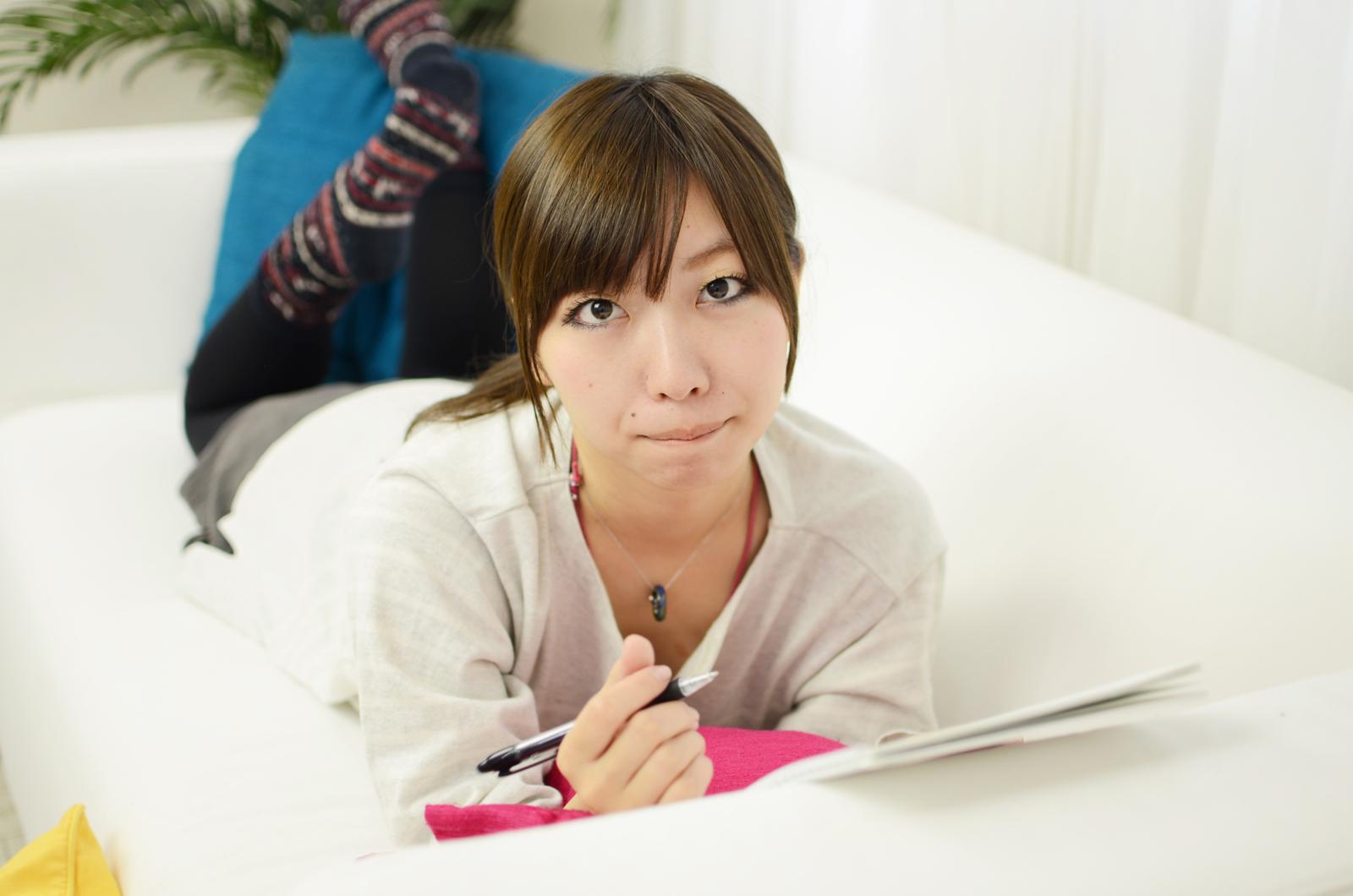ソファーで勉強する女性