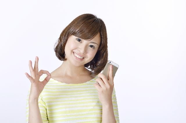 スマートフォンを持った笑顔の女性
