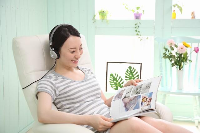 ヘッドフォンで音楽を聴きながら雑誌を読む女性