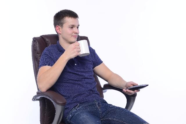 リモコンを持ってテレビを見る外国人