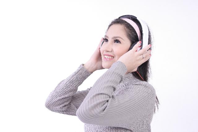 ヘッドフォンを付けた嬉しそうな女性