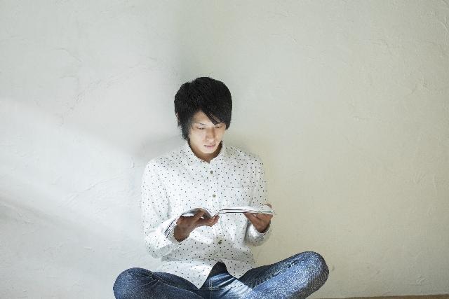 座って本を読む若い男性