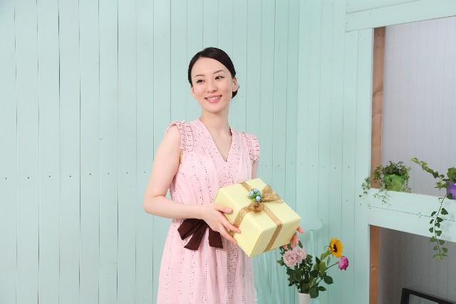ワンピースを着てプレゼントを持つ女性