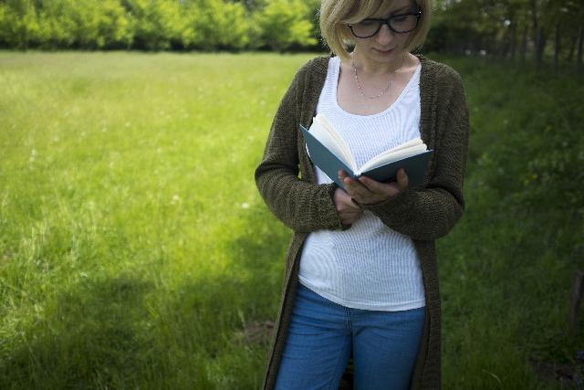 木の下で読書する白人女性