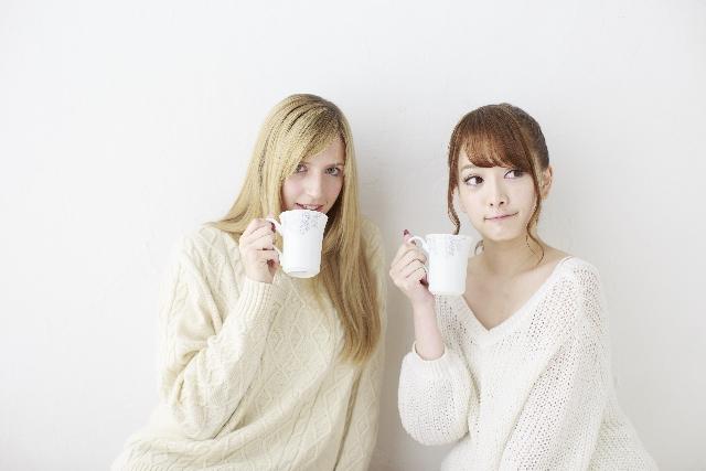 コーヒーを飲む日本人と白人の女性