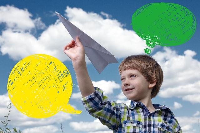 紙飛行機を飛ばす白人の少年