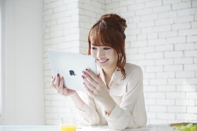 笑顔でタブレットを使う女性
