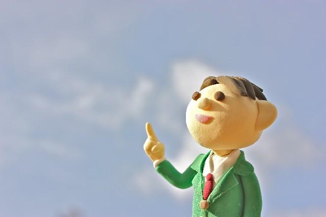空を背景に指をさす人