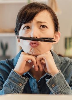 鼻の下にペンを挟んで考える女性
